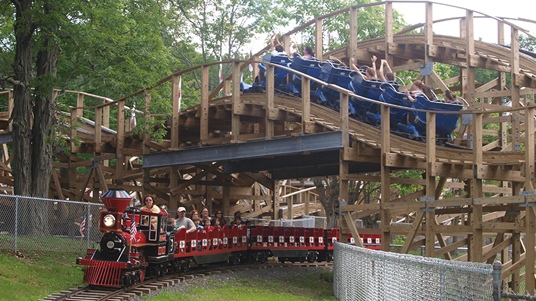 People in blue cars riding the Wooden Warrior roller coaster as people in red cars ride the Quassy Express Train